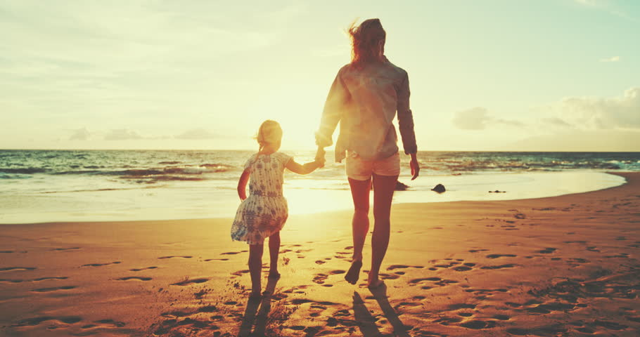 Mother and daughter walking and playing on the beach at sunset