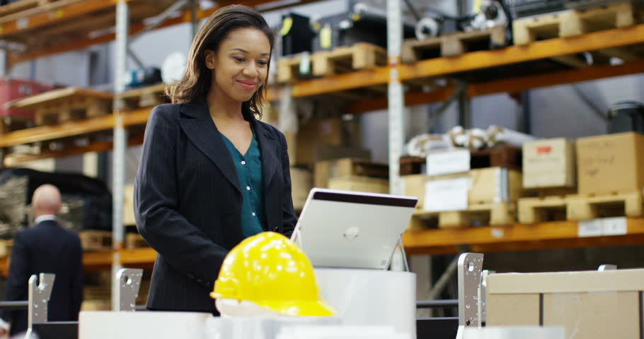 4k, Happy and cheerful female warehouse employee working on a laptop computer and checking stock. In slow motion.