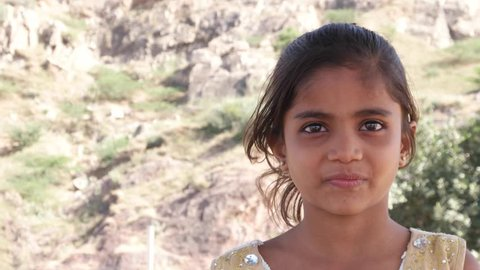 Little cute Indian girl watching something and getting frightened but happy and smiling still