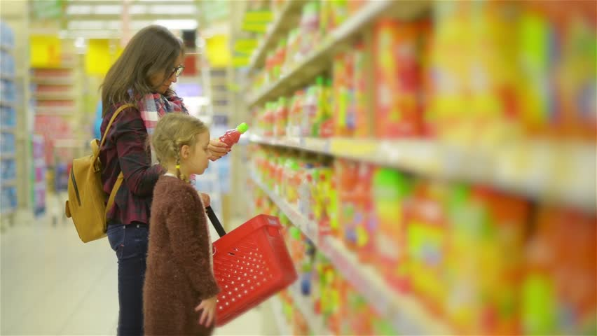 Young Wife and Cute Girl Standing Near Shelf with Goods in the Supermarket. Mom with Child Shopping together in Juice Section at a Store. | Shutterstock HD Video #22084264