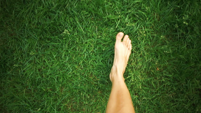 Bare feet walking on the grass POV, concept of freedom and happiness