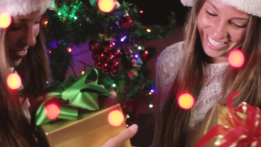 Twin Sisters Decorating Christmas Tree And Giving Each Other Gifts | Shutterstock HD Video #22147234