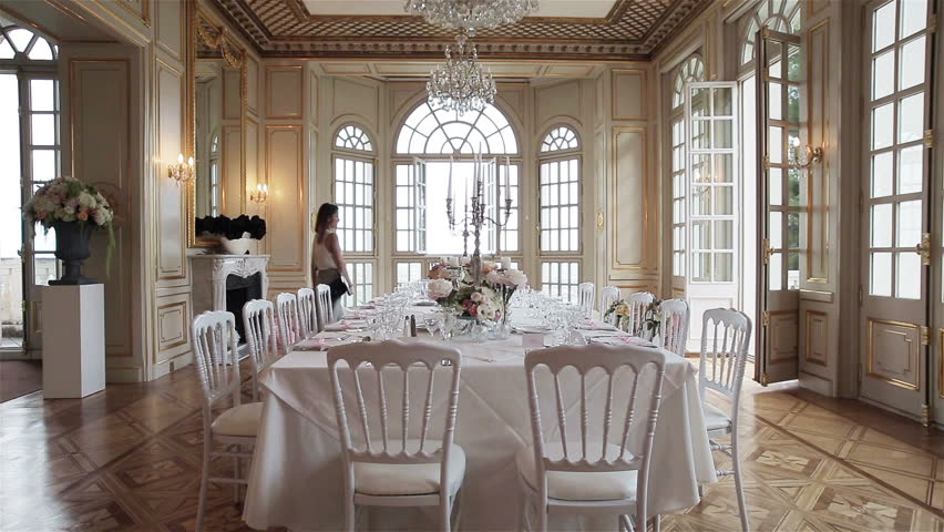 Woman catering manager or wedding planner walks around festive table set decorated for wedding banquet celebration in luxury room dining hall interior. Decoration of events stylish table arrangement