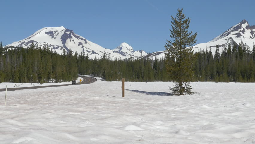 Zoom and tracking view of Cascade Lakes Scenic Byway with Three Sisters and Broken Top in the background, from Dutchman Flat, near Bend, Oregon.