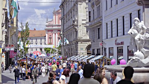 LJUBLJANA, SLOVENIA - AUGUST 2016: Static long shot with Robba fountain in right side of frame and focus on orange church at Preseren square. Crowd of people walk bellow. Sound included.