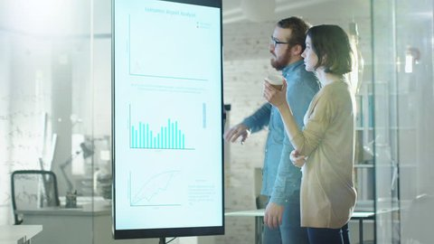 Young Man and Woman Discuss Charts Drawn on Their Electronic Whiteboard. Man Shows Details on the Screen Woman Listens Holding Cup of Coffee in Her Hands.Their Office is developer and Modern Looking.
