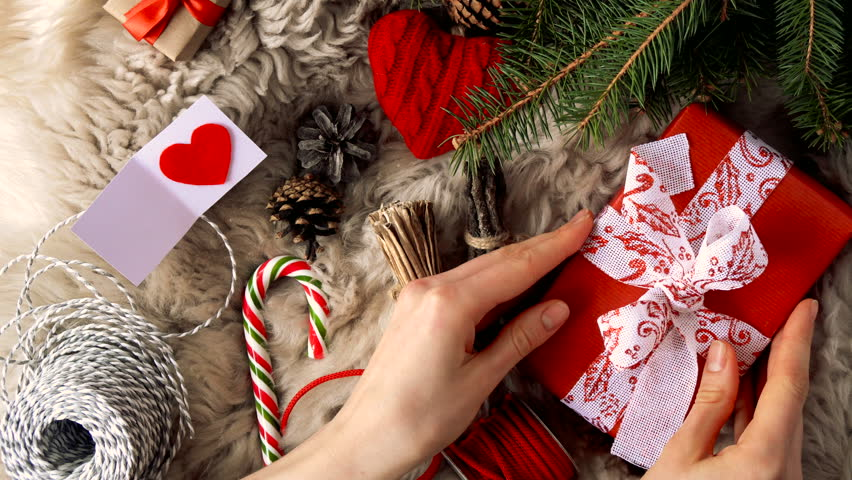 young woman hands put wrapped in red kraft paper gift o fur coat near the christmas and new year decor and than put be happy card on the gift