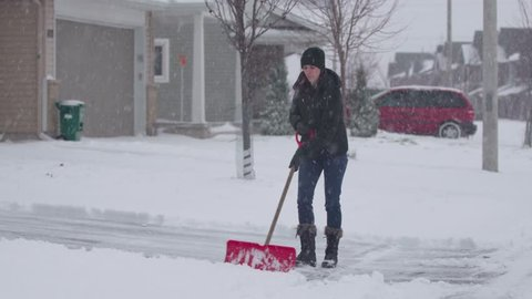 A wide shot of a woman shoveling her driveway during a snowfall.
