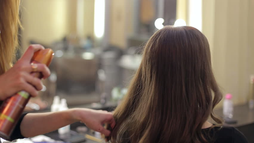 Close-up of hairdresser's hands using hairspray on client's hair at salon. Hairdresser fixing woman hair with hairspray. Beauty salon.