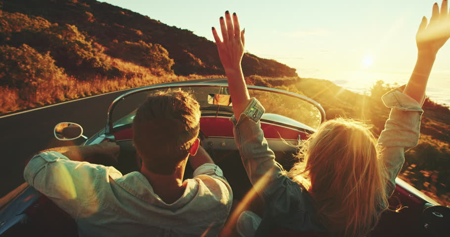 Happy couple driving on country road into the sunset in classic vintage sports car | Shutterstock HD Video #22242874