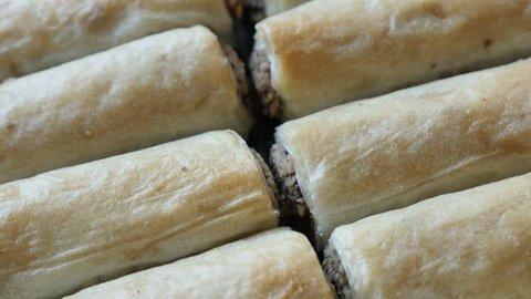 Turkish phyllo pie baklawa with walnuts 4K 2160p 30fps UHD tilting footage - Arabic dessert filo dough sweet rolls baklavas filled with nuts slow tilt 3840X2160 UltraHD video