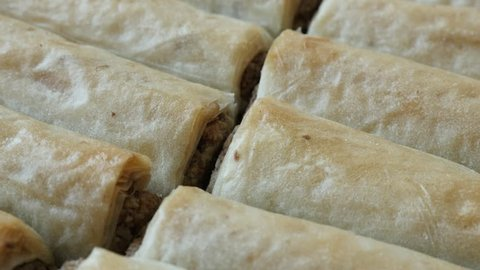 Slow pan on Eastern filo dough sweet baklawa rolls filled with nuts 4K 2160p 30fps UHD  footage - Panning on Turkish phyllo pie baklava dessert with walnuts  close-up 3840X2160 UltraHD video