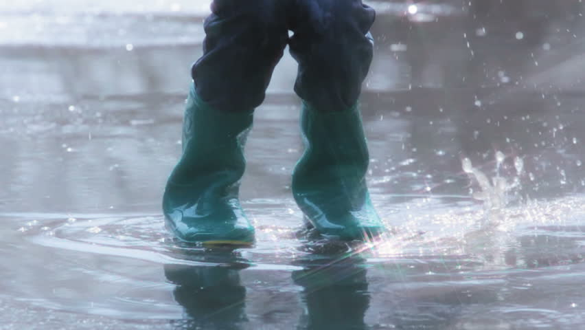 Slow motion of a child in rubber boots jumping in the middle of the puddle