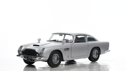 KAMPEN, THE NETHERLANDS - DECEMBER 15, 2016: Aston Martin DB5 James Bond classic sports car scale model car rotating against a white background.