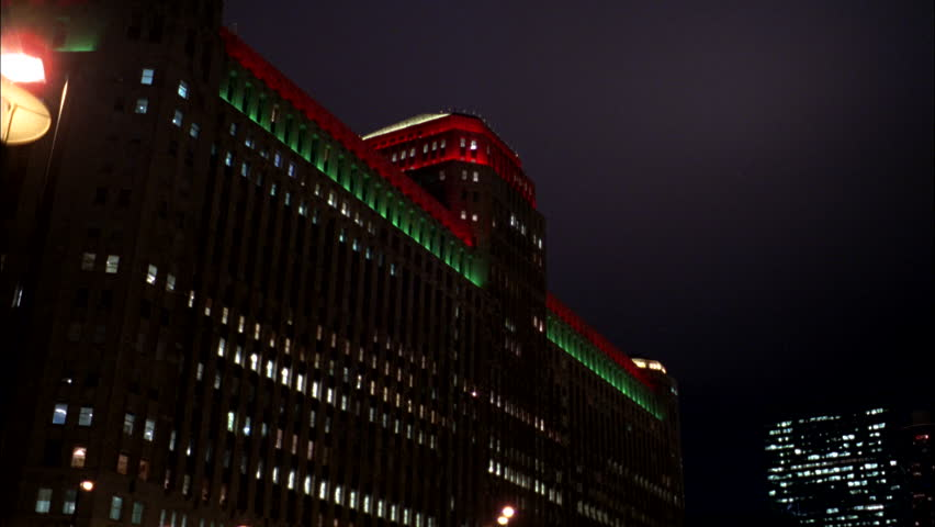 night Tilt down right large downtown office building red green accent lights Christmas raked left bridge with city street over water Cars thru, Chicago (Nov 2005)