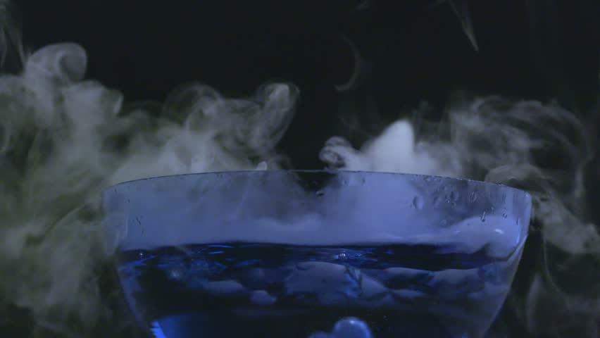 Slow motion bubbling, smoking bowl in macro on black background.