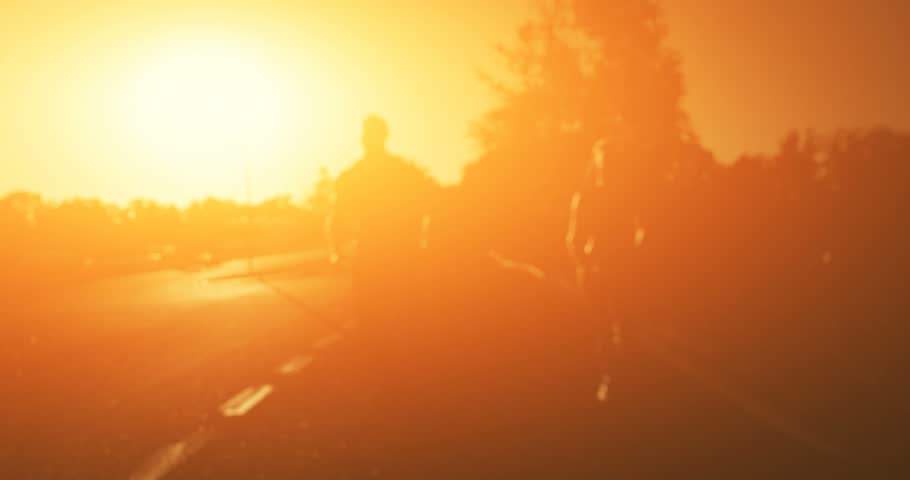 4K shooting: Young couple running in the park. Athletic attractive people jogging in summer enjoying their healthy lifestyle. Front view. Video processed in orange glow | Shutterstock HD Video #22340950