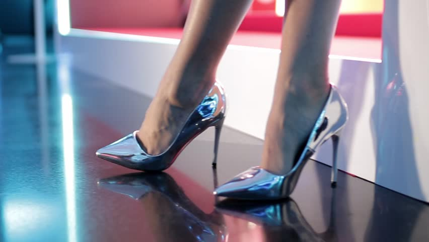Close-up shot of a pair of beautiful female legs wearing high silver heels walking away from to the camera. Zooms in to follow.