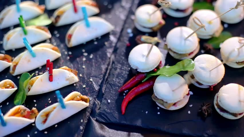 Catering for party. Close up shot of many various appetizers on a dark table. Colorful tasty canapes.