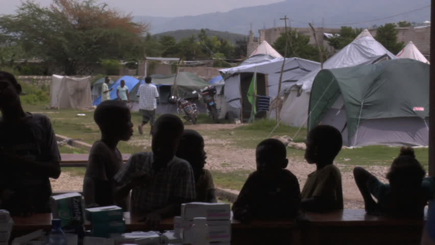 PORT-AU-PRINCE - CIRCA OCTOBER 2010: Young Haitian boys hanging around at a medical clinic in their tent city in Tabarre in Port-au-Prince, Haiti circa October 2010.