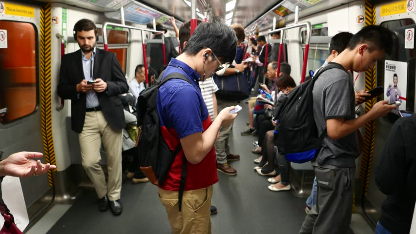 HONG KONG - MARCH 31, 2015: Young man stand in metro carriage, look to smart phone listen headphones. Mass Transit Railway in HK, train travelling through island line station, flickering outside