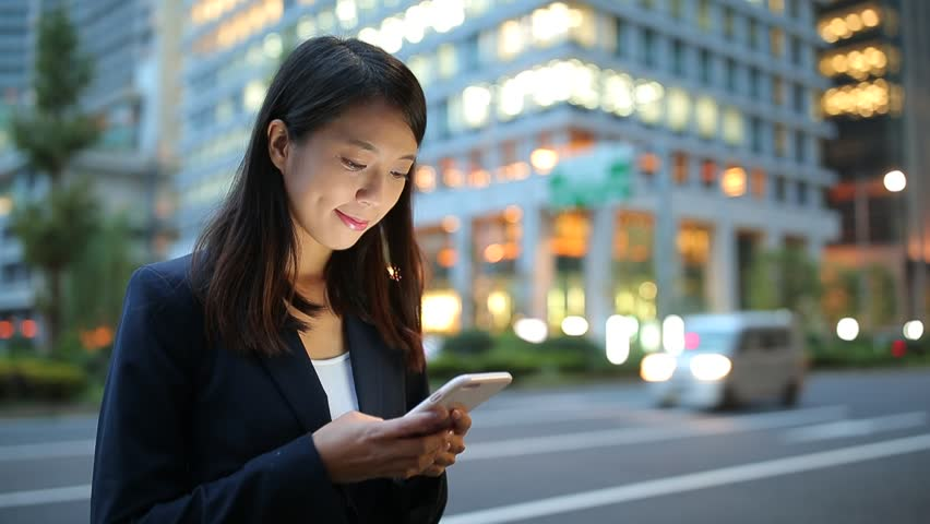 Businesswoman looking at mobile phone at evening