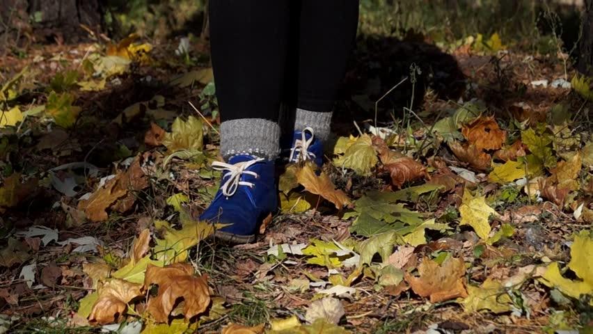 Woman`s Blue Boots Shuffling in Autumn Forest. Closeup.
