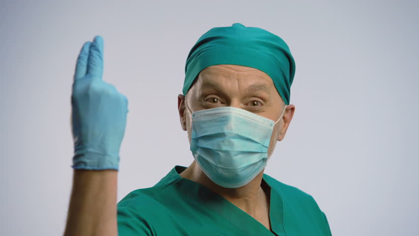 Funny man wearing scrubs and face mask pretending to be proctologist, crazy joke