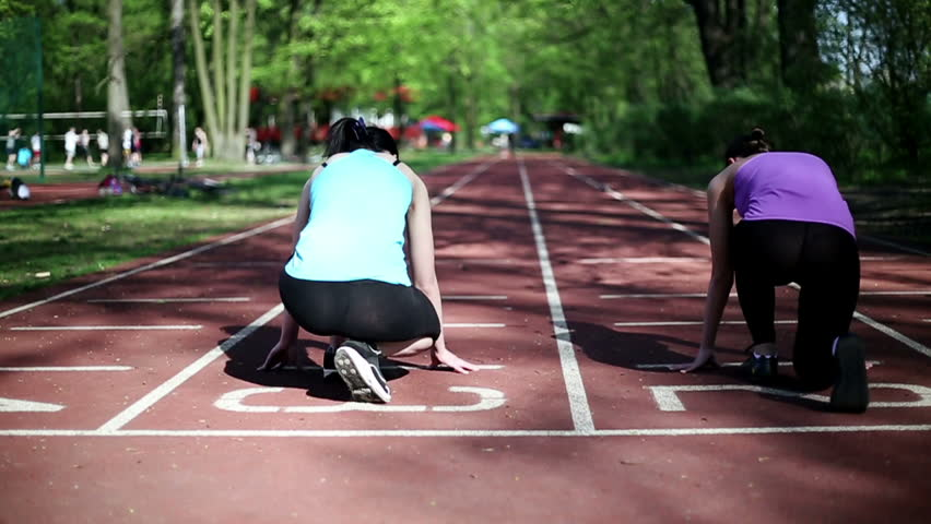 Two young women running on track lane, slow motion, dolly shot