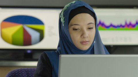 Young woman wearing hijab working at her computer