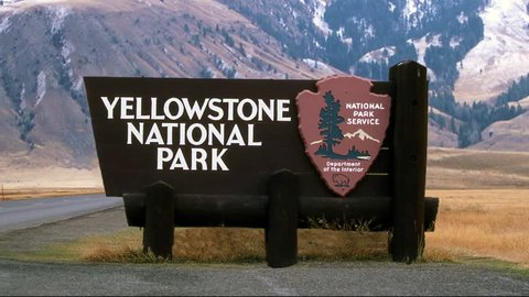 Jib reveal of Yellowstone National Park Sign, revealing gorgeous mountains and plains in the distance.