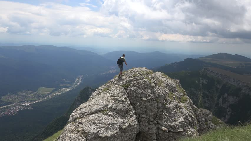 CARAIMAN MOUNTAINS, ROMANIA - Circa JULY 2016:Man climbing on top of a cliff and makes a gesture with hands.View of Busteni town, Romania, near to Heroes Cross , Caraiman Mountains, Romania, 4k, UHD | Shutterstock HD Video #22454674