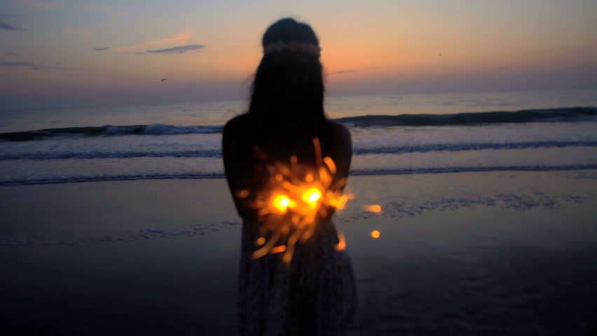 Silhouette of slim Asian Indian female enjoying 4th July party with sparklers on the beach at sunset
