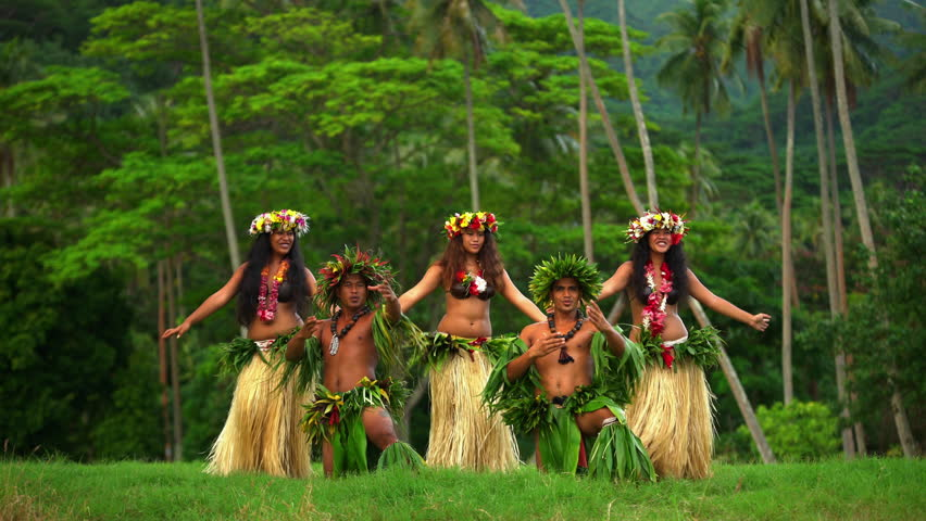 Young strong males with female group of Tahitian hula dancers performing outdoor barefoot in traditional costume Tahiti French Polynesia South Pacific