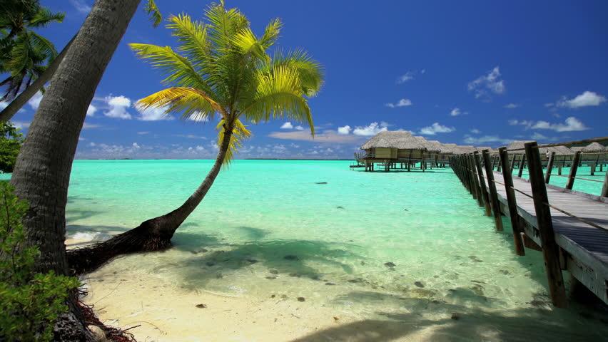Overwater boardwalk luxury Bungalows in tropical Aquamarine lagoon beach vacation resort of Bora Bora South Pacific French Polynesia