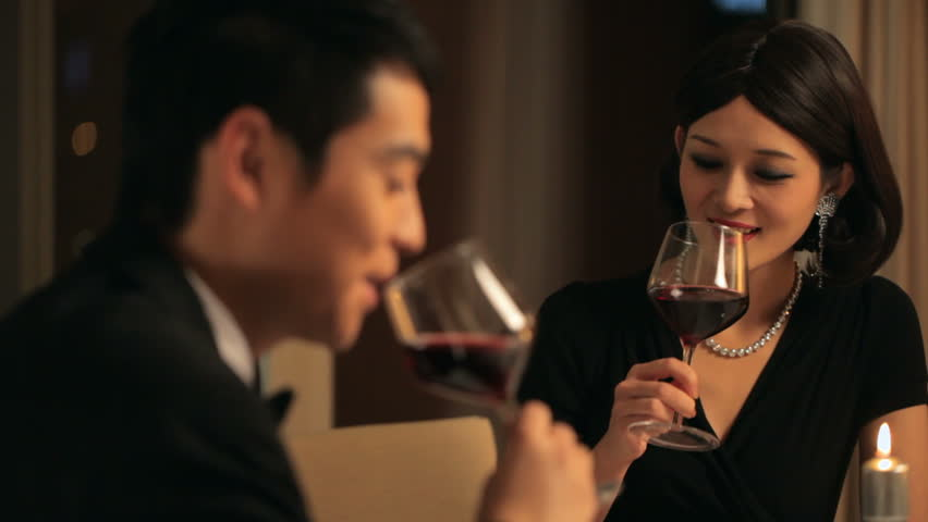 MS Couple toasting with wine glasses at candle lit dinner / China