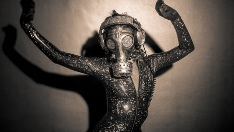 Sexy woman dances with a gas mask covered in sparkling crystals. how to survive the apocalypse in bling bling style.