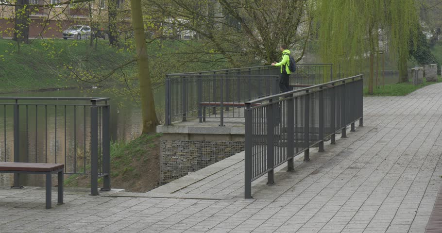 A Tall Man Leans on a Metal Fence, Behind Which a River Begins. the Man is in a Green Zone of a City of Opole (Poland). he Stands on a Bridge and Beholds a Flow of Water. | Shutterstock HD Video #22511758