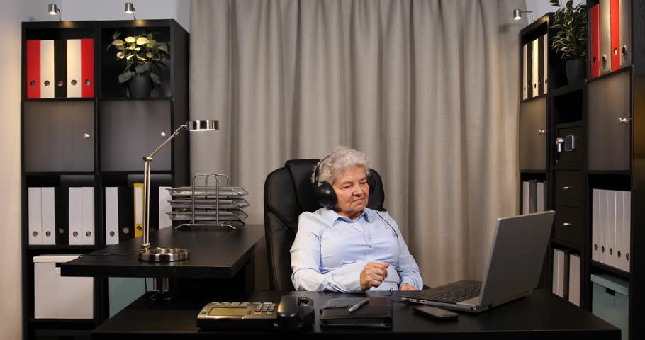 Older Pensioner Woman Listen Music Audio Book Using Headphones Laptop Computer Ultra High Definition