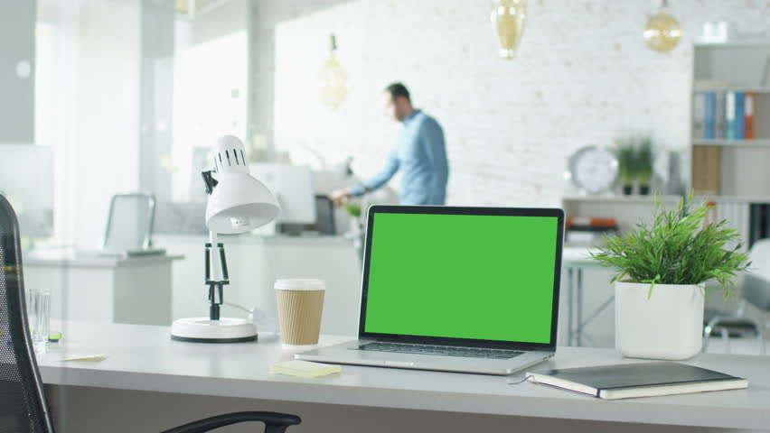 Creative Office Shot of Green Screened Laptop Standing on the Table with Nobody Working on It. In the Background Man Comes in and Sits at His Workplace Starts Working. Shot on RED EPIC (uhd). | Shutterstock HD Video #22521094