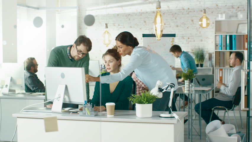 In Brightly Lit and Modern Creative Bureau. In Foreground Three People Discuss Business Issues Using Desktop Computer. In Background Groups of Coworkers Discuss Work. Shot on RED EPIC (uhd). | Shutterstock HD Video #22521130