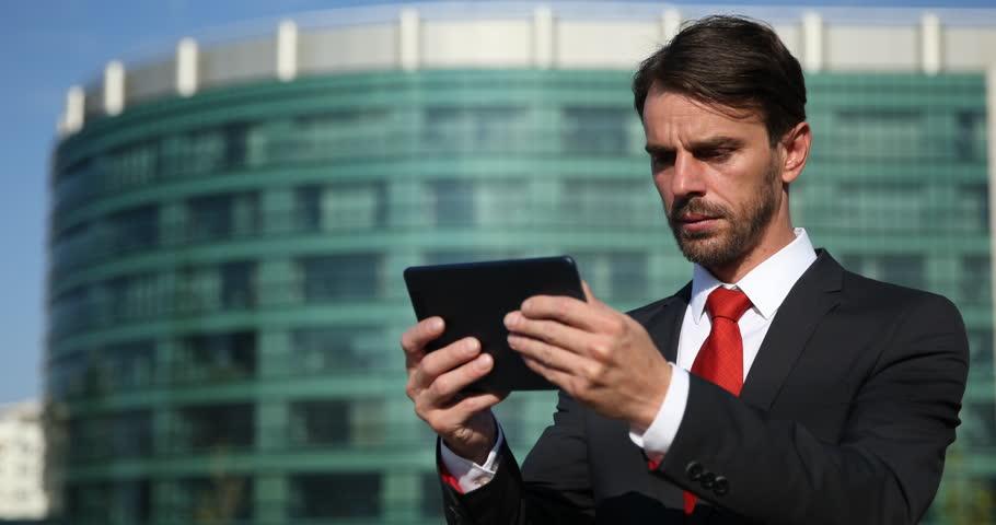 professional male teacher explaining main ideas of essay making inspector business man browsing digital tablet upset moment corporation building ultra high definition ultrahd
