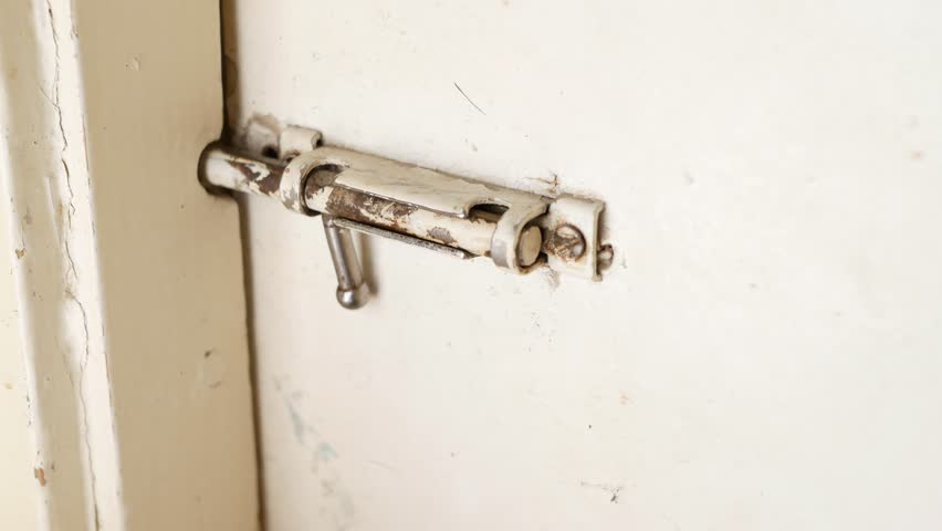 Man unbolting an old sliding lock and opening a door.