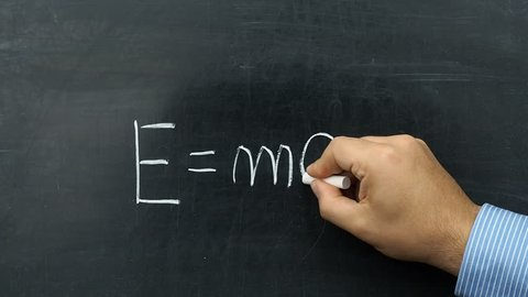 Famous Albert Einstein s equation E=mc2 handwritten on chalkboard or blackboard by teacher or businessman