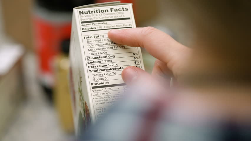 Female shopper reading nutritional information on a box of crackers.