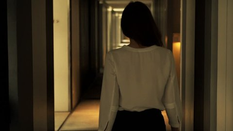 Elegant, young woman walking through hall in hotel