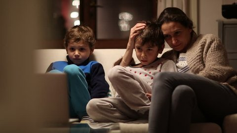 Mother and children watching TV screen at the living room. Mom with concerned look in her face worried about the content they are watching