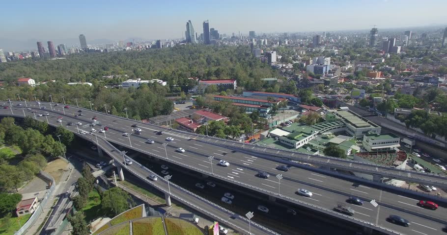 A fast flyover of Mexico City features a highway with traffic as well as the Children's museum --or Museo del Niño-- as well as the downtown skyline.