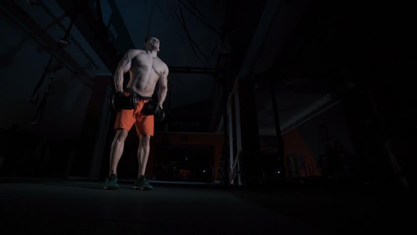 Strong slender man raises dumbbell | Shutterstock HD Video #22592014