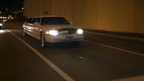 limousine driving through urban city night limo